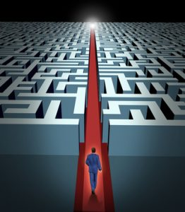 Leadership and business vision with strategy through corporate challenges and obstacles represented by a maze and a business man in a labyrinth with a clear solution shortcut path opened with a red velvet carpet to lead the way to success and victory.